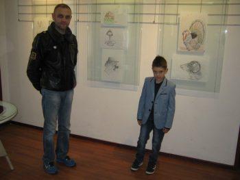Vukašin i njegov otac Milovan pored crteža izloženih u Galeriji KCK FOTO: CINK - S.Milenković